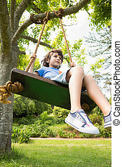 Low angle view of a cute little boy on swing