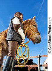Low angle view of a girl and her horse