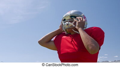 American football player putting on his helmet - Low angle ...