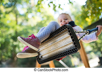 Low angle view of a small toddler girl on a swing on a playground.