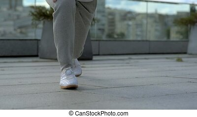 Low angle view of a sporty man doing squates with lunges -...