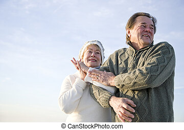 Low angle view of affectionate mature couple arm in arm -...