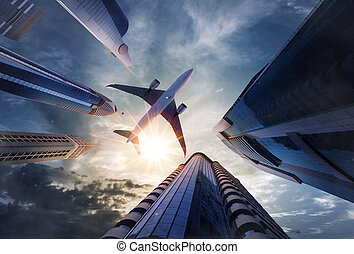 Low angle view of airplane above skyscrapers