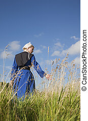 A low angle view of an Amish girl walking in a field touching the grass