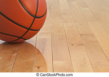 Low angle view of a basketball on a wooden gymnasium floor