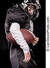Low angle view of boy american football player holding rugby ball