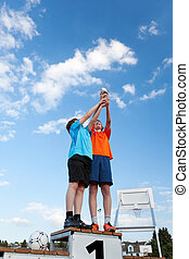Low angle view of boys holding trophy while standing on winners podium against sky