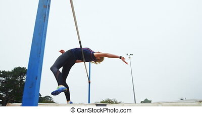 Low angle view of Caucasian female athlete practicing high jump at sports venue. Beautiful sky in the background 4k