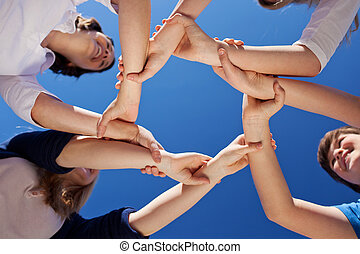 Low angle view of children and teacher forming frame while holding hands against clear blue sky