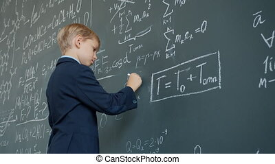 Low angle view of clever schoolboy writing formulas with ...