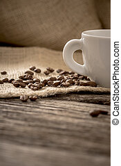 Low angle view of coffee beans scattered on linen cloth lying on textured wooden desk