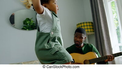 Low angle view of cute little black son dancing on the floor in living room of comfortable home 4k