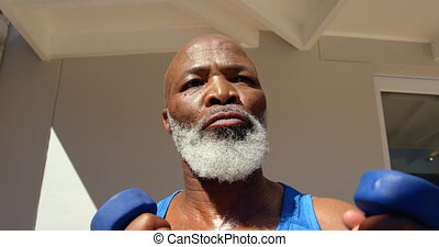 Low angle view of determined mature black man exercising in ...