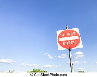 Low angle view of do not enter sign with tree top under cloudy sky