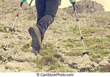 Low angle view of female ascending a rocky slope using walking poles.