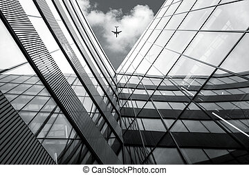 Low angle view of flying airplane over modern architecture...