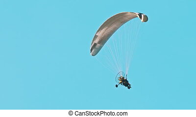 Low angle view of flying paramotor in air. Parachute against blue sky. Tandem motor powered paragliding at twilight.