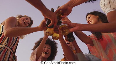 Low angle view of friends toasting on the beach - Low angle ...