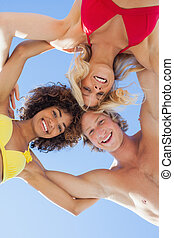 Low angle view of happy friends on beach