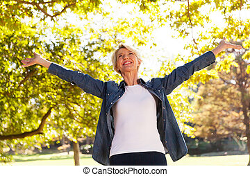 mid age woman with arms outstretched outdoors - low angle...