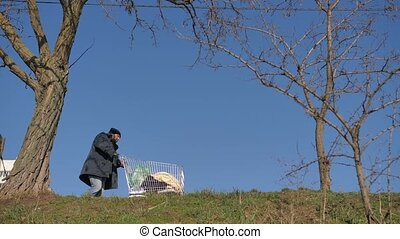 Low angle view of homeless man pushing cart - Low angle full...