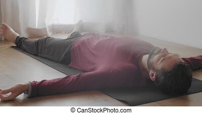 Low angle view of man relaxing in shavasana asana indoors natural morning light. Bearded Caucasian instructor lying on yoga mat after practice slow motion. relaxation meditation stress overcome