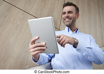 Low angle view of man with digital tablet