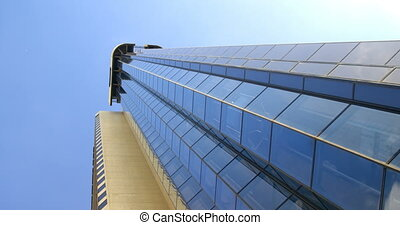 Low angle view of modern office building. Beautiful and clear sky in background 4k