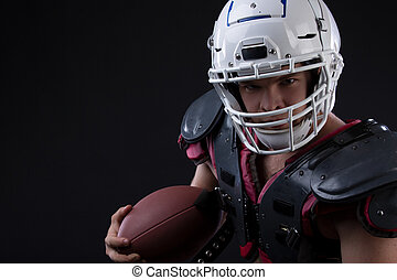 Low angle view of muscular american football player in uniform and helmet holding ball