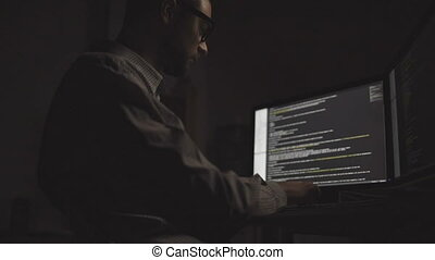 Low angle view of professional hacker working