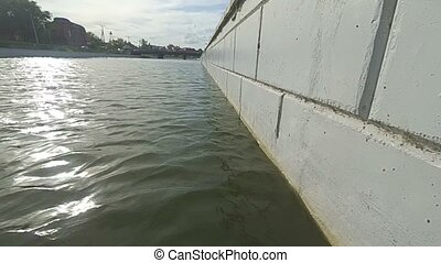 low angle view of river water surface and cement wall, slow...