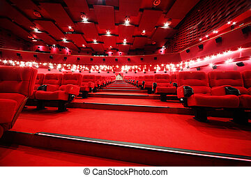 Low-angle view of stairs between rows of comfortable red chairs in illuminate red room cinema