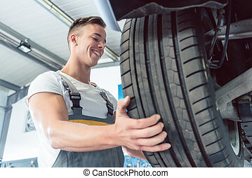 Low-angle view of the hand of a skilled auto mechanic holding a tire
