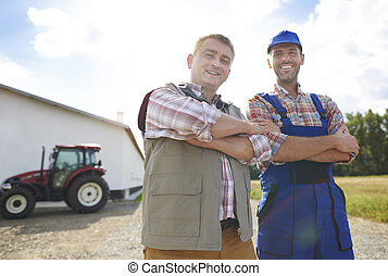 Low angle view of two cheerful farmers