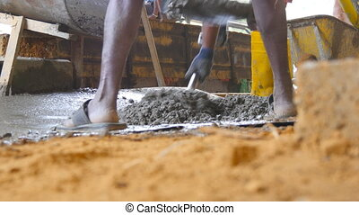 Low angle view of unrecognizable indian men shoveling manually wet cement in pile at building site. Local builders working on construction area. Concept of future project. Close up