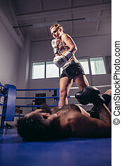low angle view of woman boxer celebrating victory while man lying on ring floor