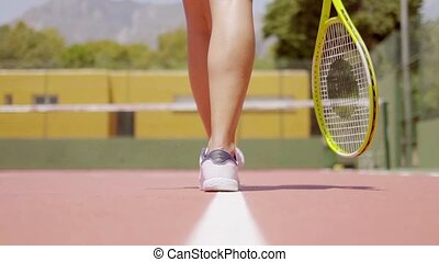 Low angle view of woman walking a line drawn on a tennis...