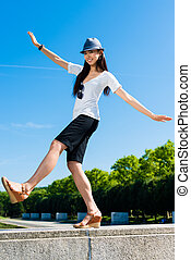 Asian woman standing on one leg outdoors
