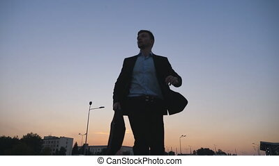 Low angle view of young businessman in a formal black suit...