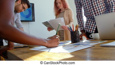 Low angle view of young mixed-race business team working in meeting room of modern office 4k