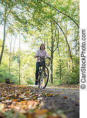 Low angle view of young woman riding a bicycle