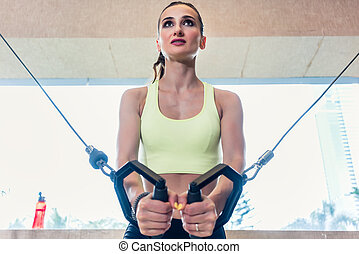 Low-angle view portrait of a cheerful beautiful woman exercising
