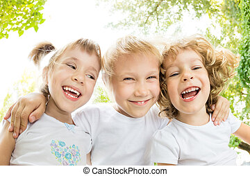 Low angle view portrait of happy children laughing outdoors...