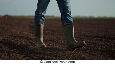 Low angle view Slow motion. Follow to male farmers feet in boots walking through the small green sprouts of sunflower on the field. Legs of young man stepping on the dry soil at the meadow