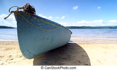 Low angle view to anchored laminate blue rowing boat at...
