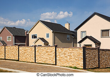 Low beige stone fence on background of new two-storied cottages.