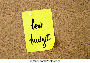 Low Budget written on yellow paper note pinned on cork board with white thumbtacks, copy space available