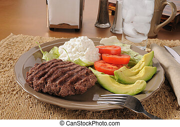 A grilled hamburger patty with avocado, tomato and cottage cheese
