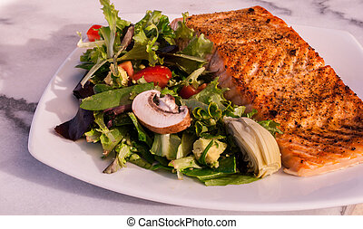 white plate of organic salad with a large piece of salmon filet. Low carb, weight loss, diet, isolate, close up