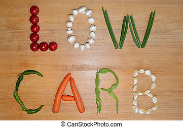 The text 'low carb' written with fresh vegetables on a wooden background.